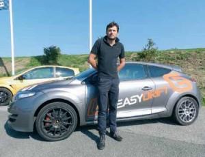 Evens Stievenart devant l'une des voitures de sport.