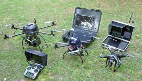 Ici, plusieurs drones civils aériens avec le matériel adéquat : le poste de commande avec l'écran pilote et de deux stations de bases (réception des vidéos).
