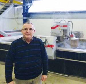 Marc Gense devant sa machine découpe jet eau 3D.