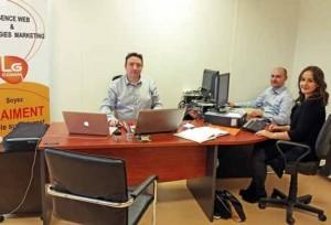 Luc Gautron derrière son bureau avec à ses côtés son employé et sa stagiaire.