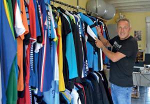 Patrick Devisme devant ses t-shirts et polos en exposition dans son showroom.